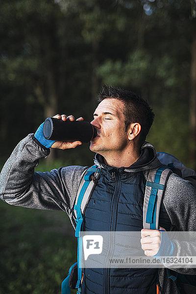 Man camping in Estonia  drinking water
