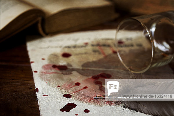 Letter on parchment paper with blood drops  fallen whiskey glass and quill