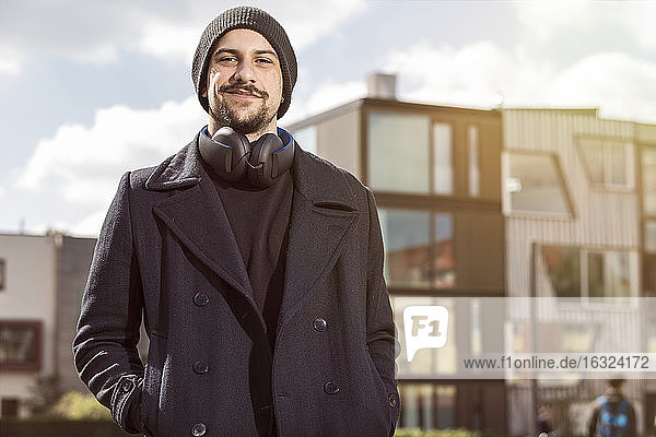 Portrait of smiling young man with headphones wearing wool cap and black clothes