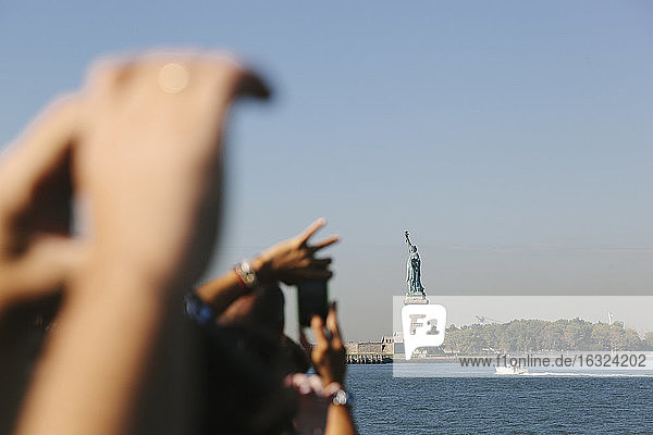 USA  New York City  tourists taking picture of Statue of Liberty