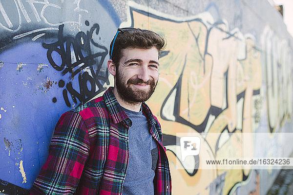 Spain  La Coruna  portrait of smiling hipster