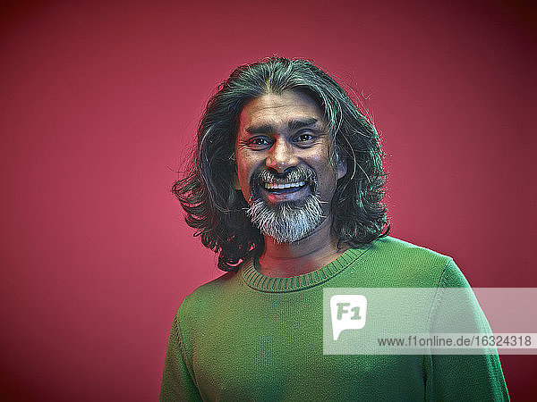 Portrait of smiling man in front of red background