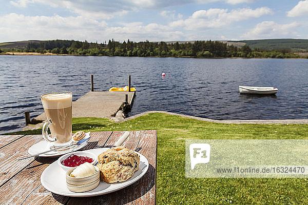 United Kingdom  Scotland  Highlands  Latte Macchiato and scone with clotted cream and jam