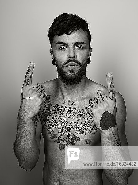 Portrait of man with tatoo on his chest and hands