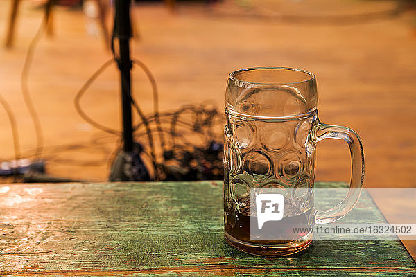 Germany  Munich  Oktoberfest  Beer jug on wooden table  stage equipment in background
