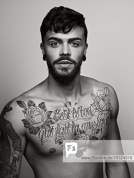 Portrait of man with tatoo on his chest and upper arm