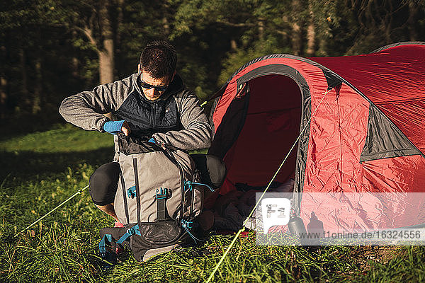 Man camping in Estonia  searching his backpack