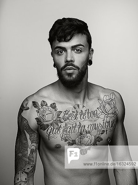 Portrait of man with tatoos on chest and upper arm
