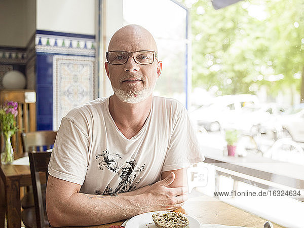 Germany  Berlin  Mature man sitting in cafe  looking at camera