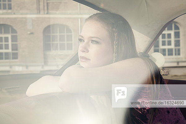 Young woman looking through window of vintage car