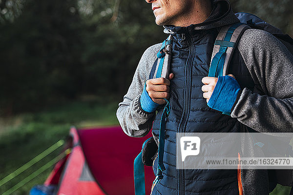 Man camping in Estonia  leaving camp with backpack for a hike