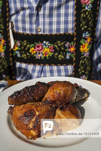 Germany  Munich  Oktoberfest  Man with half a chicken on plate