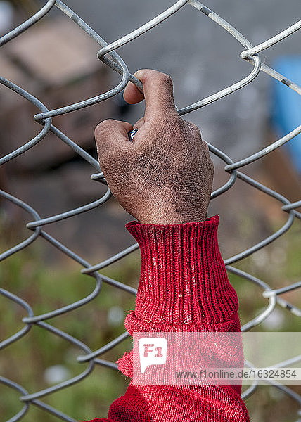 Close-up of hand at mesh wire fence