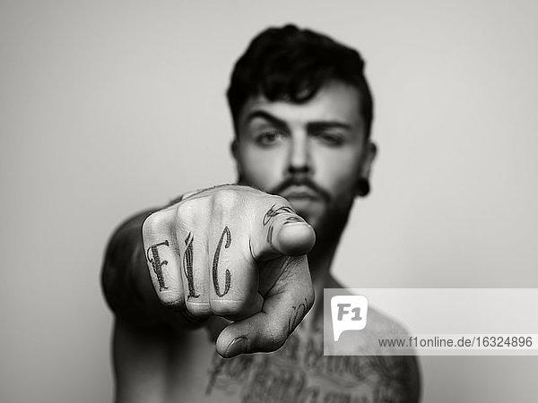Man's tatooed hand pointing on viewer