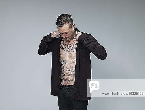 Man with tattoo on his waist up dressing black shirt in front of grey background