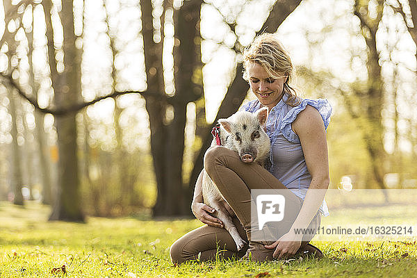 Smiling woman with piglet in park