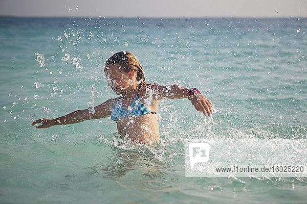 Tanzania  Zanzibar Island  girl spashing in the sea