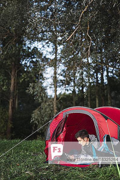 Man camping in Estonia  sitting in his tent  using smartphone
