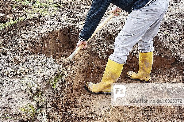 Mann gräbt eine Pflanzenterrasse an einem Teich aus Mann gräbt eine Pflanzenterrasse an einem Teich aus