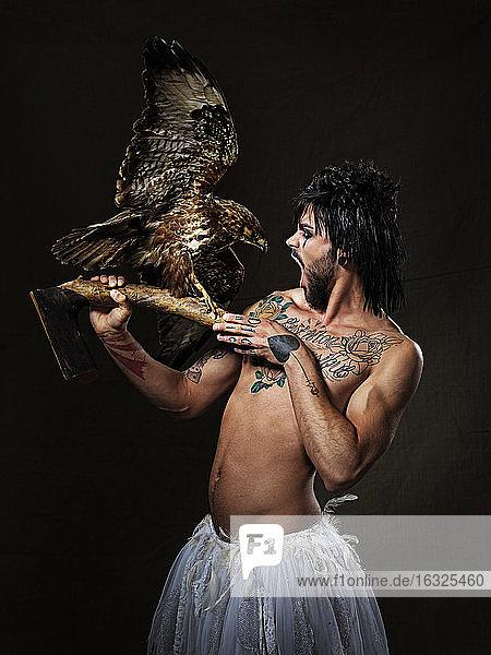 Shirtless man with full beard and eye make up wearing totu holding eagle preparation