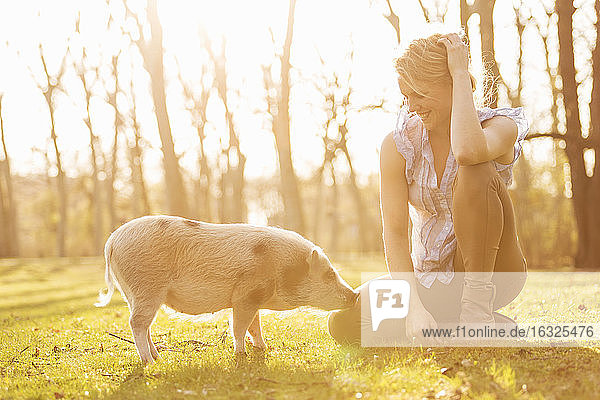 Smiling woman sitting with piglet in park