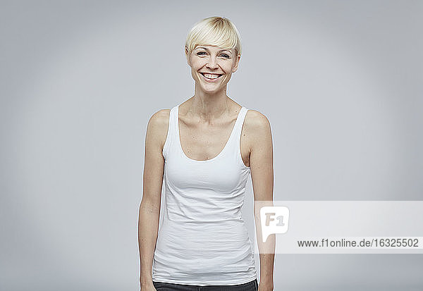 Portrait of happy blond woman wearing white top in front of grey background