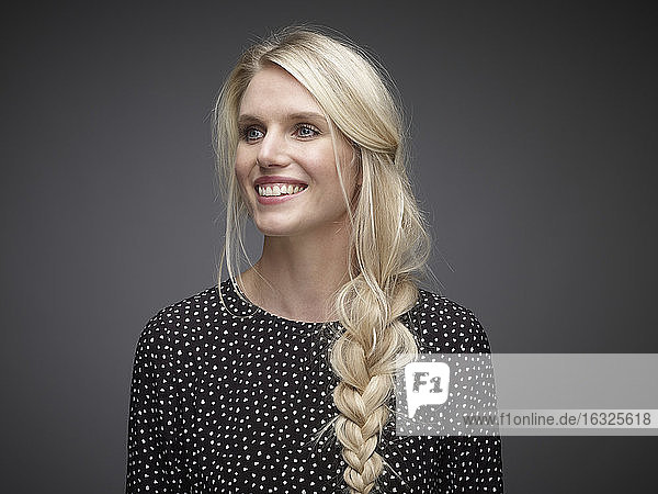 Portrait of smiling blond young woman with braid in front of grey background