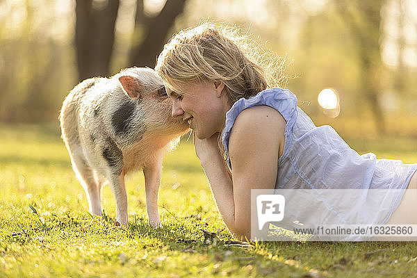 Smiling woman lying with piglet in park