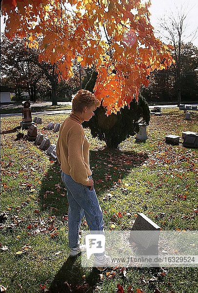 Female visits a grave site of a loved one in a cemetary with colorful tree in background.