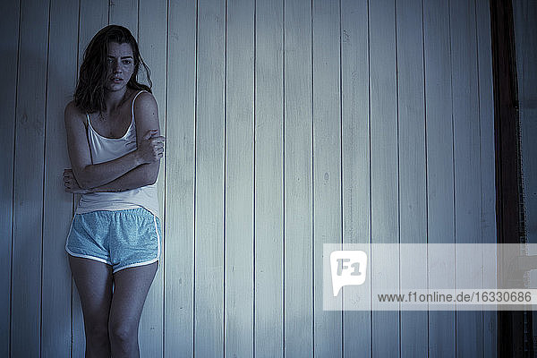 Sad young woman standing in bedroom