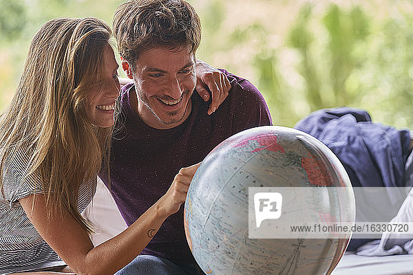 Young couple exploring world globe while sitting on sofa