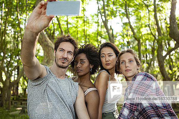 Young friends taking selfie on smartphone outdoors