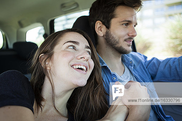 Cheerful young couple holding hands in car