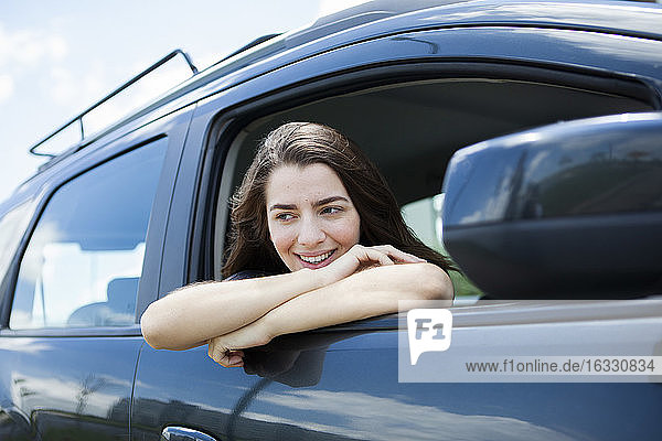 Beautiful smiling young woman sitting in car