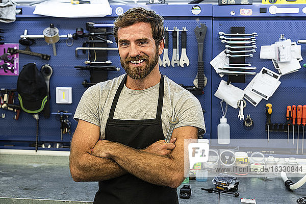 Smiling mechanic standing in workshop