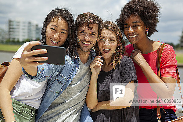 Happy young friends taking selfie on smartphone