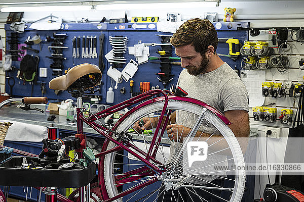 Mechanic repairing bicycle in workshop