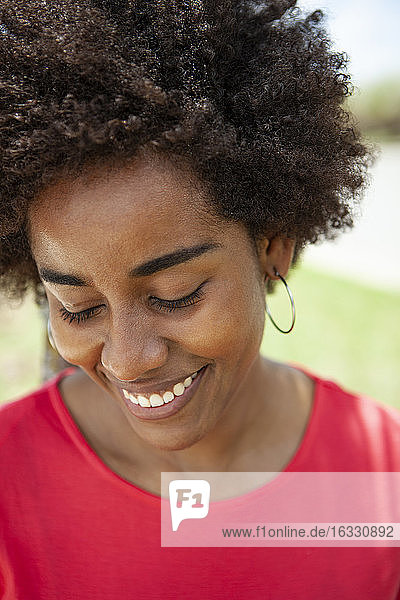 Portrait of smiling young woman standing in park