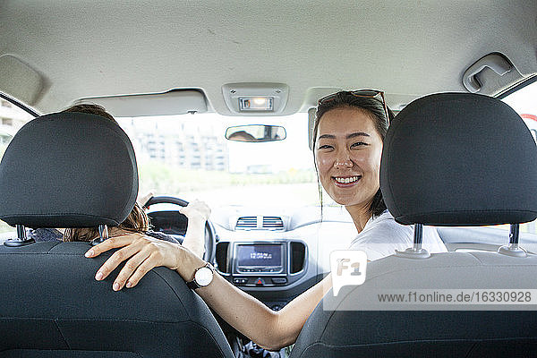 Smiling young woman sitting in car with a female friend