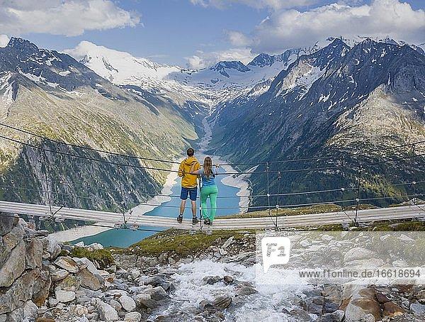 Wanderer  junge Frau und junger Mann auf Hängebrücke an der Olpererhütte  Ausblick auf Schlegeisstausee  Speicher Schlegeis  hinten Zillertaler Alpen mit Gletscher Schlegeiskees  Zillertal  Tirol  Österreich  Europa