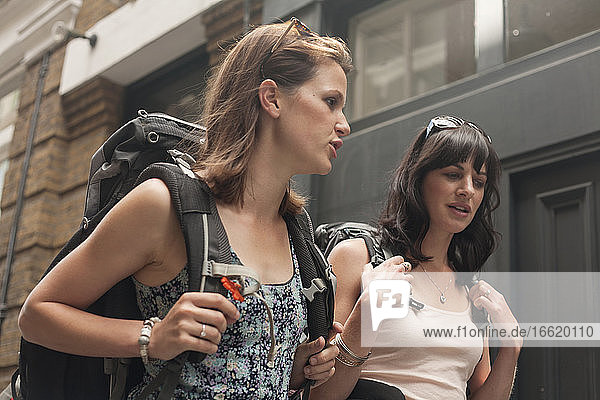 Beautiful female backpackers talking while walking in city