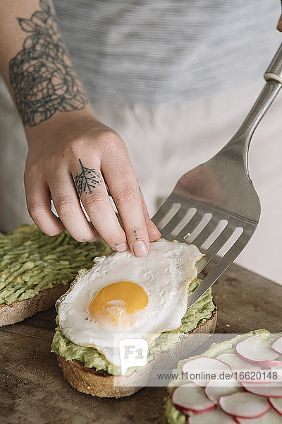 Woman garnishing omelet on guacamole spread bread while standing at kitchen