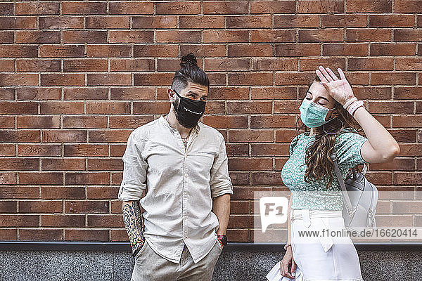 Couple wearing protective face masks while standing against brick wall during COVID-19