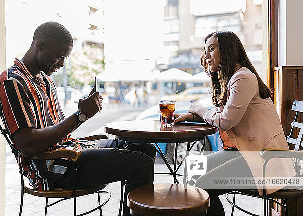 Freund  der seine Freundin mit dem Smartphone fotografiert  während er am Tisch im Café sitzt