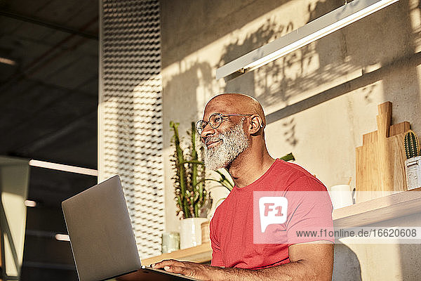 Smiling mature man looking away while using laptop at home on sunny day