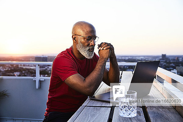 Mature bearded man looking at laptop while sitting on building terrace in city during sunset