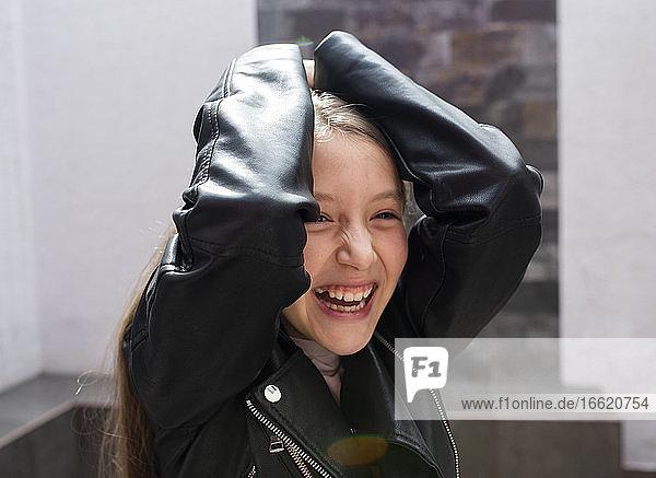 Lächelndes Mädchen mit Jacke  das zu Hause steht