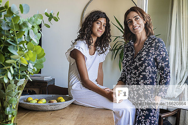 Smiling mother standing by daughter holding fruit while sitting on table at home
