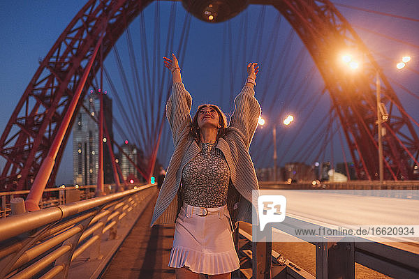 Cheerful woman standing with arms raised on bridge in city at night