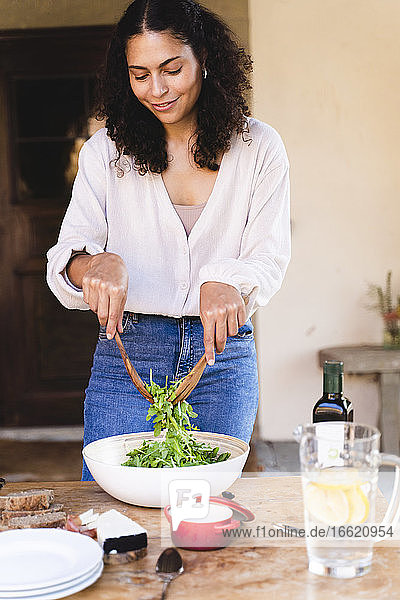 Beautiful woman preparing salad while standing by table at backyard
